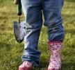 Kid in a garden holding gardening tool