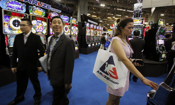 A visitor tries a slot machine at Global Gaming Expo Asia in Macau June 8, 2011. Macau, the world?s largest gaming market, looks set to maintain its explosive growth with revenue this year likely to grow by 30 percent, its gambling regulator said on Tuesday.   REUTERS/Bobby Yip   (CHINA - Tags: BUSINESS SOCIETY) - RTR2NFIU